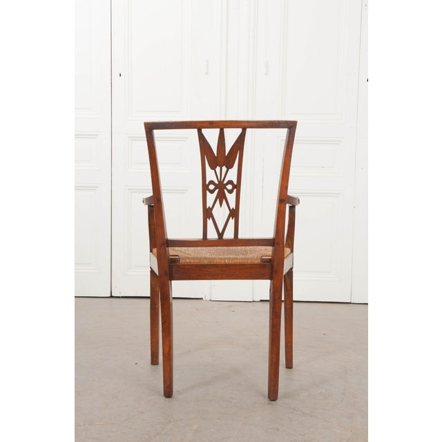 This rare Louis XVI style walnut armchair, c. 1850, is from the provincial countryside of France and features a unique...