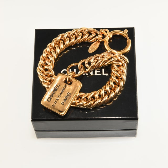Chanel bracelet with gold plated finish. Dangling tag charm reads Chanel 31 Rue Cambon Paris. Marked indicating it was...