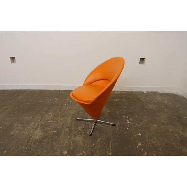 This cone shaped chair was designed by Verner Panton. It is covered in an orange vinyl and swivels.
