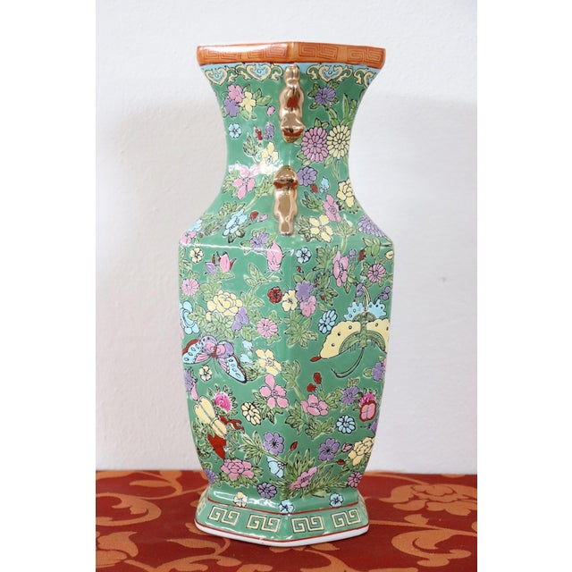 Refined polychrome ceramic vase China, 1960s. Main color green with beautiful colorful floral motifs. Gold handles. Ideal...