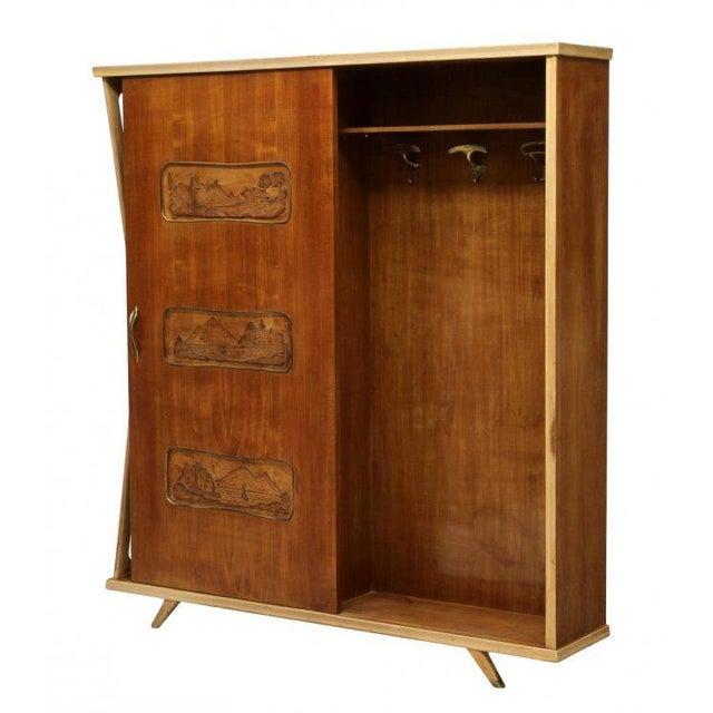 Italian mid-century modern entry cabinet, 1950's, one side with a sliding door coat closet with carved landscape panels,...