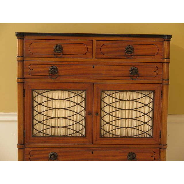 Kittinger regency style satinwood chiffonier high chest. Features dovetailed drawer construction, solid brass hardware,...