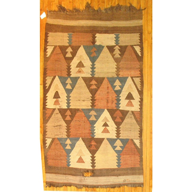 A handmade Navajo Rug with a directional motif in rustic colors.