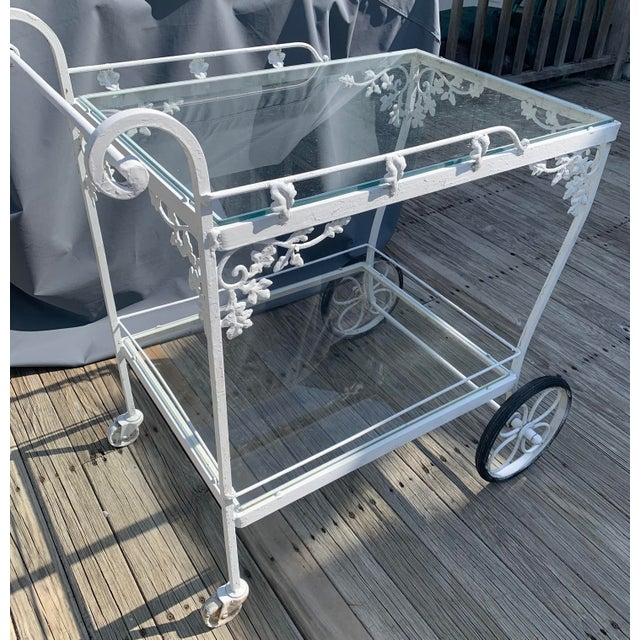 Woodard Orleans pattern wrought iron tea cart. Original white painted finish. Two removable glass shelves. Lower shelf...