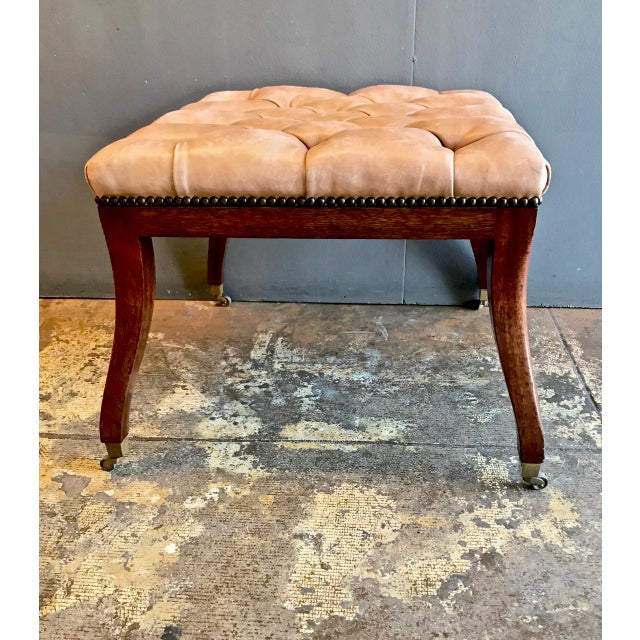 This is an unusual Regency-style bench with outswept legs terminating in small casters. The leather tufting has acquired a...