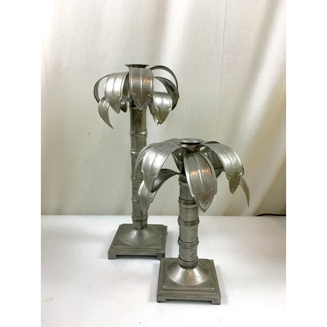 """Pair of metal palm tree shaped candleholders. Large candleholder is 14"""" H and small is 10"""" H."""