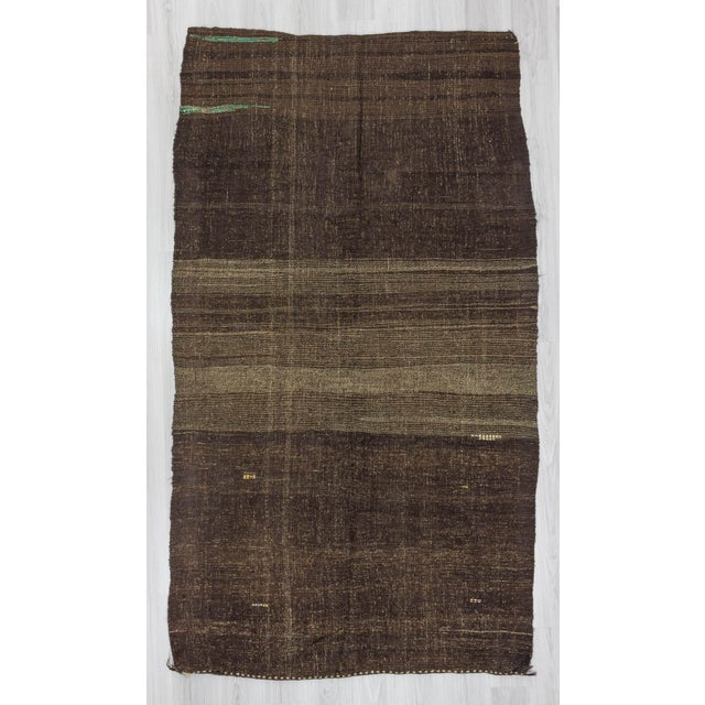 This is a handwoven brown kilim rug from the Afyon region of Turkey. In good condition. Approximately 45-55 years old.