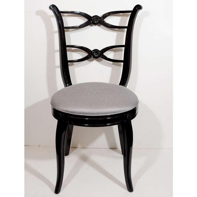 This pair of 1940s Hollywood chairs with stylized lyre back design with double ribbon center details, in ebonized walnut...