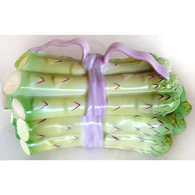 A small, covered dish by Herend in the form of asparagus wrapped with a pink ribbon. The bottom piece is decorated...