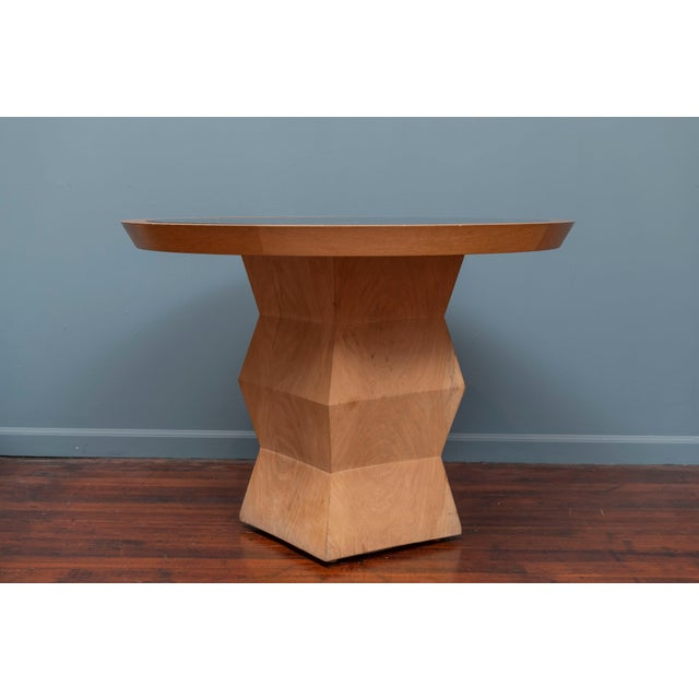 Christian Liaigre design Yquem pedestal table in solid oak with adapted black granite and oak top. Small wood chip on...