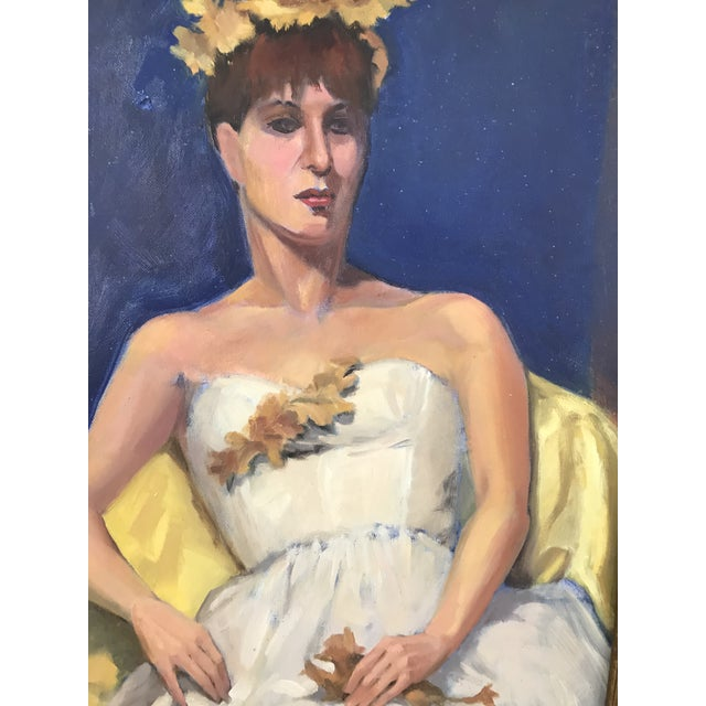 Regal woman wearing a white dress and leaf crown. She's sitting in a yellow chair with a blue / navy background. She's...