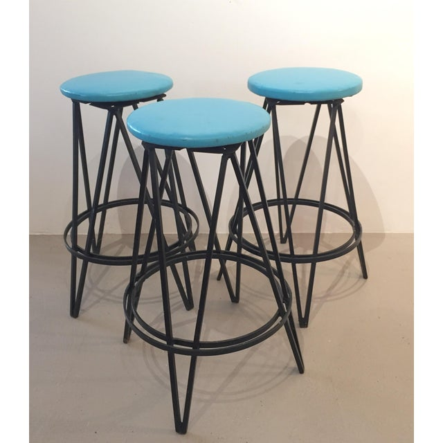 Charming set of three iron base swivel stools. Great architectural form to the heavy black iron bases. Seats upholstered...