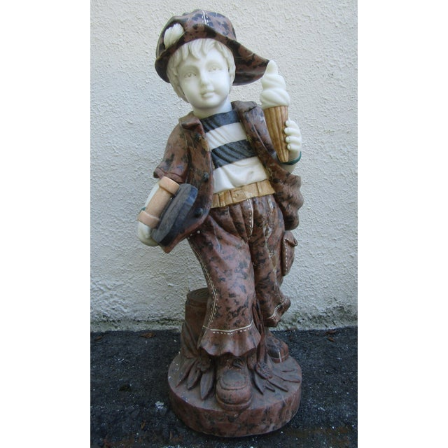 A wonderful stone statue of a boy holding a skateboard and an ice cream cone. The skillful design boasts incredible detail...