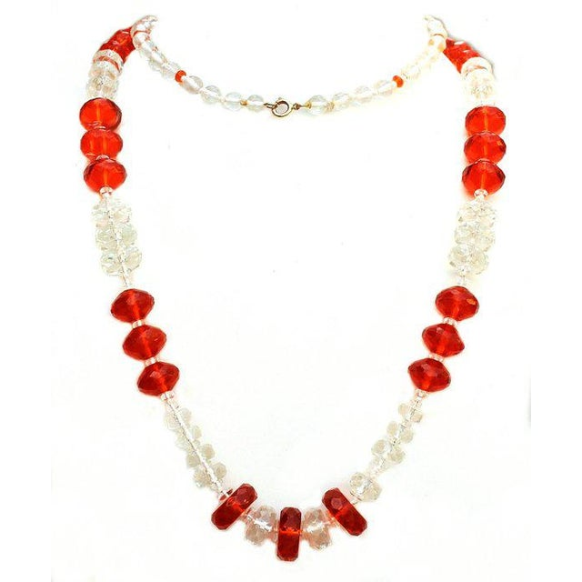 Fabulous c.1930s long hand knotted bright orange and clear faceted glass beads in multiple shapes and sizes. The necklace...