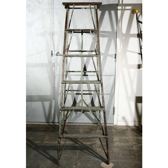 A vintage folding ladder, now suited as a stand for display, circa 1930's, with an old worn paint finish. Having a lot of...