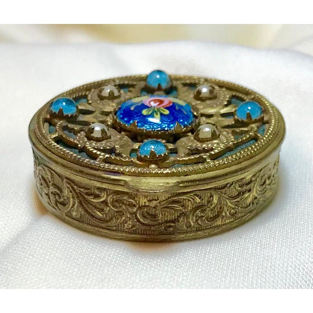Circa 1920s French ornately designed gold tone powder compact. The top has an openwork design over a blue-green fabric and...