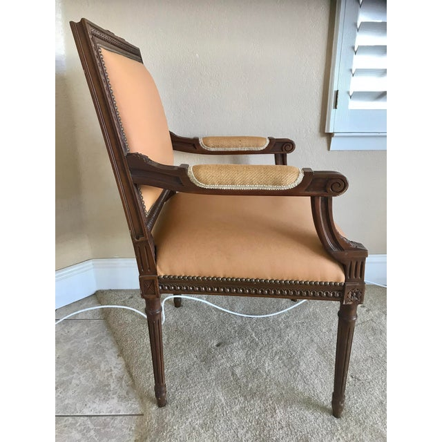 A pair of French Louis XVI style chairs with Leather and nailhead trim. Carmel in color, dark brown wood construction....