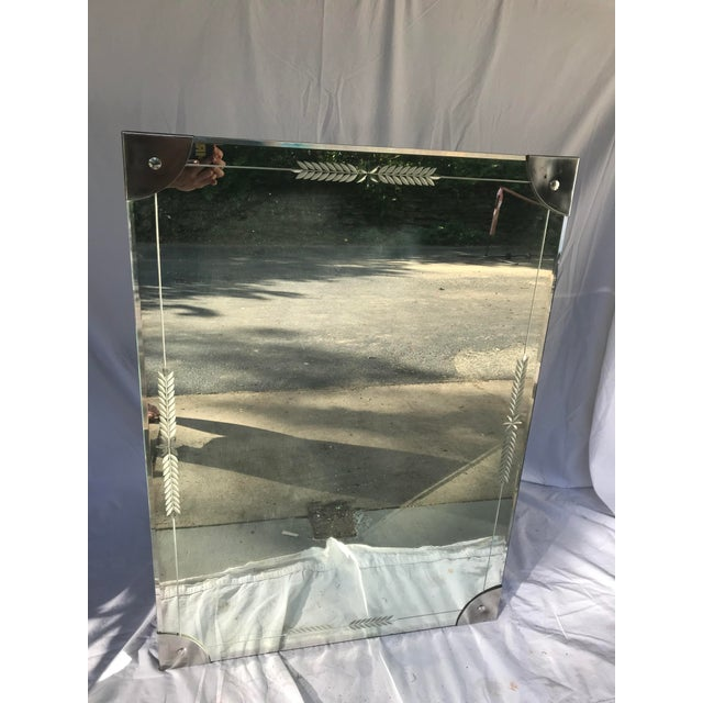 Vintage mid-century Etched/Cut glass mirror with demi lune metal corners. Mirror could be oriented either way. Stamp on...