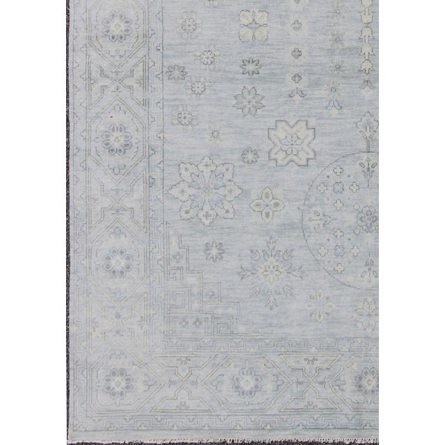 This hand-woven Indian Khotan rug features a beautiful geometric design in shades of gray. Measures: 8'11 x 11'11