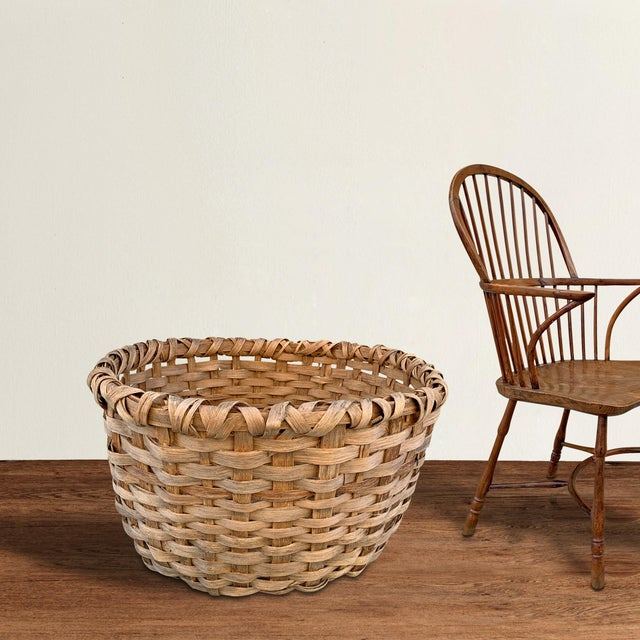 A massive late-19th century American oak splint basket with a double-banded rim and likely used for storing wool in a...