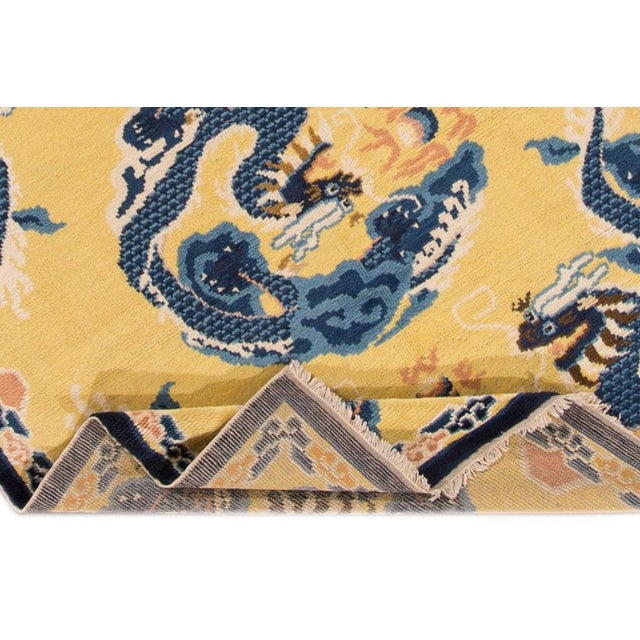 A beautiful antique Dragon Peking Chinese hand-knotted Wool rug with a yellow field and multi-color accents all-over...
