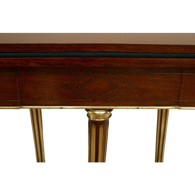 French Louis XVI mahogany and inlaid flip top demilune shaped console card table. With brass fluted legs and trim with...