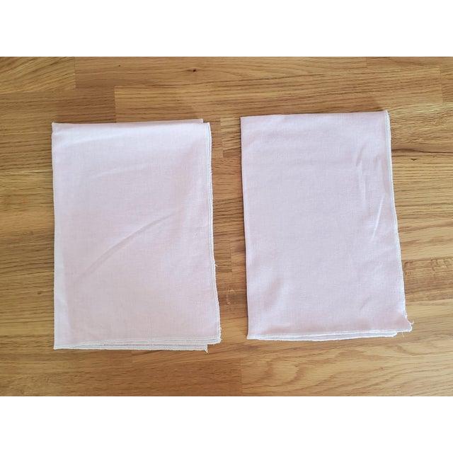 This pair of tea towels, kitchen towels, or dish towels are made of an apparel weight linen in light pink. The edge is...