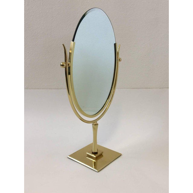 "A glamorous polished brass with copper color leather covered back. ""Wish Bone"" vanity mirror by Charles Hollis Jones...."