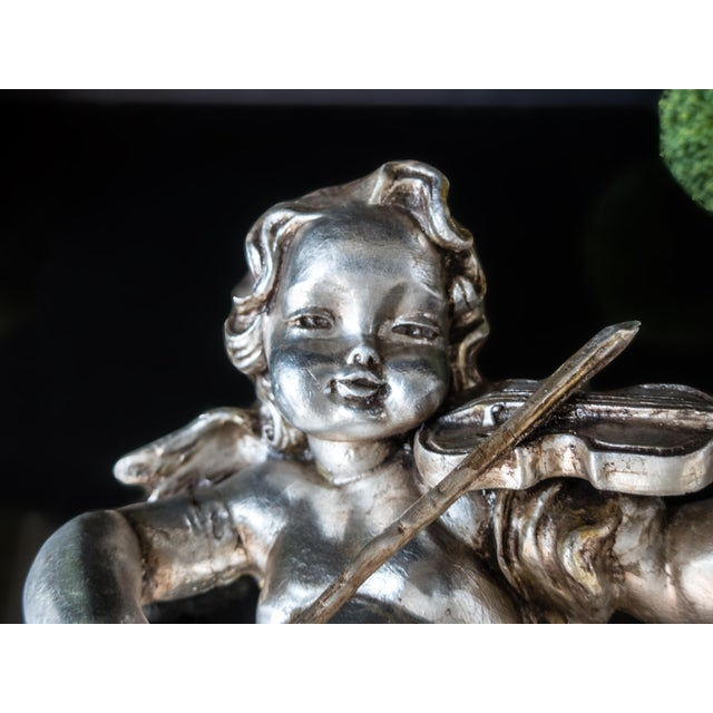 Breathtaking, almost life-size, paper mache, silver leafed, cherub playing the violin. This large sculpture is 3...