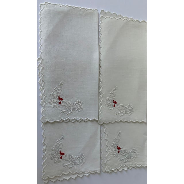 Set of 6 1950s white linen cocktail napkins with embroidered roosters. Each napkins is embroidered with a rooster, hen and...