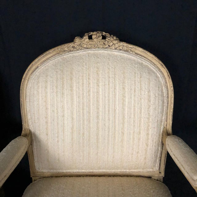 Pair of exquisite painted French bergère armchairs with ivory and cream paint and complementary upholstery, circa 1940s....