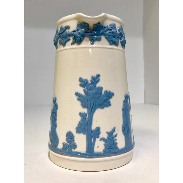A beautiful English Wedgwood pitcher. In a neoclassical style this piece features blue and white color with raised...