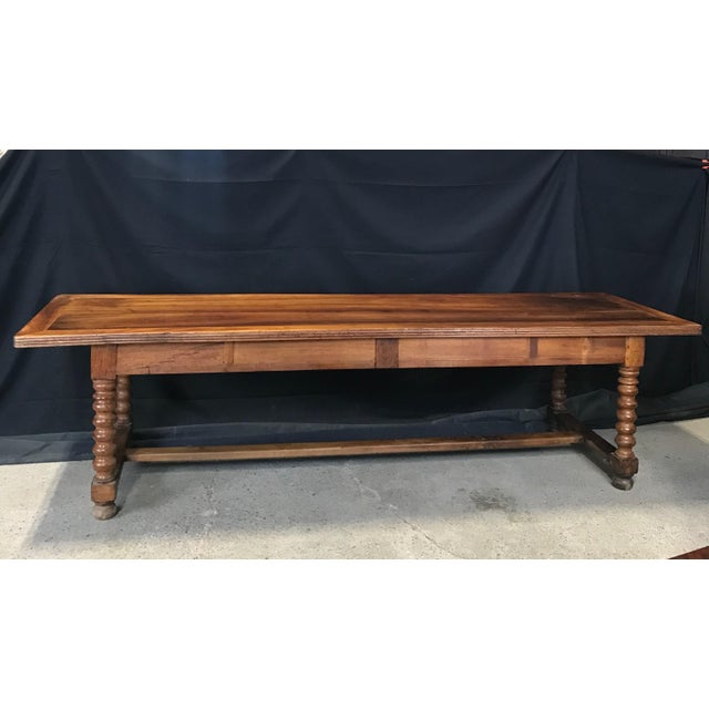 """An authentic walnut expansive 9'7"""" long farmhouse dining table having impressive turned and carved twist legs, two..."""