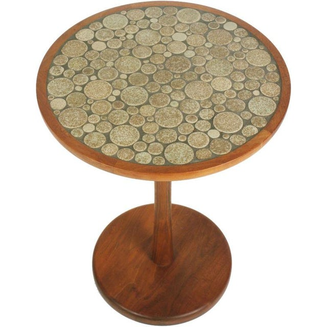 A pedestal side table with a round top inlayed with mottled taupe and brown glazed circular ceramic tiles in various...