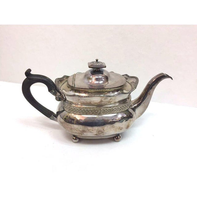 Elegant antique silver plated copper teapot with an ebony wood handle.