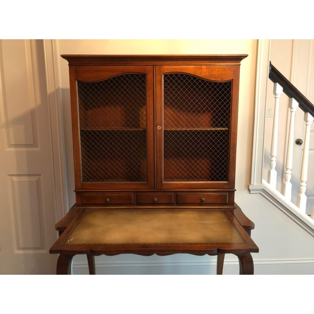 This is a lovely French country style secretary with a grated wire hutch and pull-out desk. Made by Heritage Henredon....