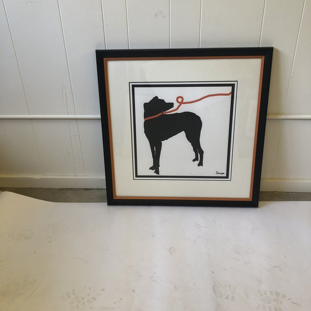 Dynamic square stylized print of a black silhouetted dog on an orange leash. The print is custom framed by black and white...