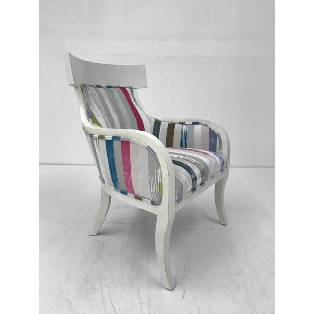 The Turnbridge Chair is a first quality market sample that features a multi-colored fabric and a Coconut Finish.