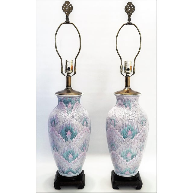 Offering a unique and colorful pair of vintage Famille Rose ceramic porcelain table lamps, circa 1960s. These beautiful...
