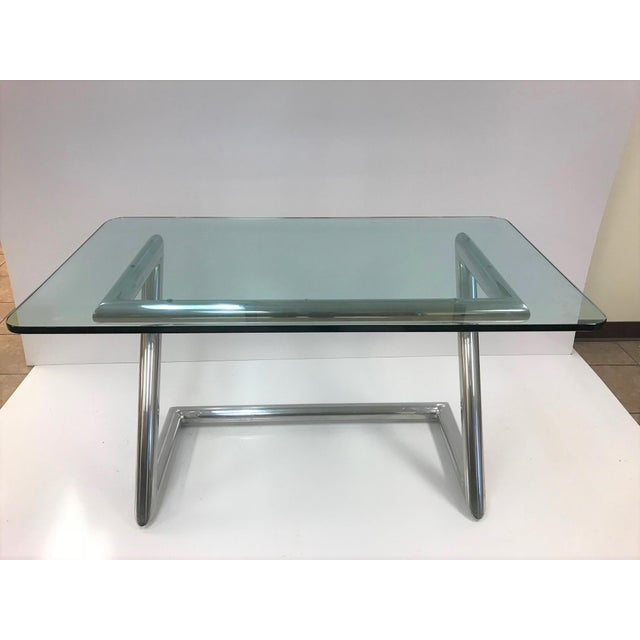 John Mascheroni polished aluminum and glass desk. Desk has a tubular frame with a 1/2 inch thick glass top.