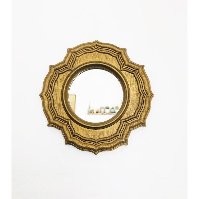 A wonderful vintage petite round mirror in an ornate frame made of resin with a faux gilt wood look.