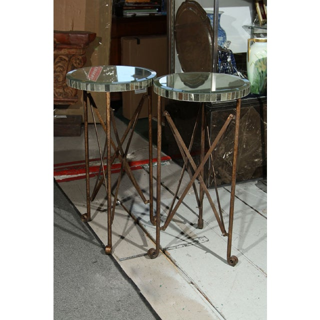 Offered is a decorative patinated metal stand on scrolled feet with circular mirrored tops. Rustic yet elegant.