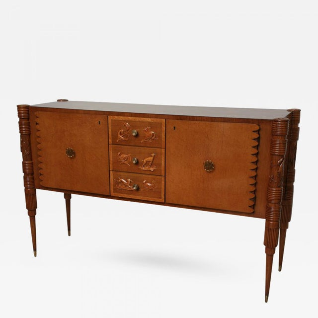 The rectangular top with rounded edges above three central drawers with animal motif flanked by two doors, the legs reeded...