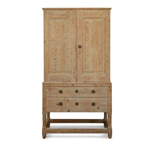 Swedish pine tall cabinet: early 19th century transitional hand-carved cabinet-on-chest raised on turned legs. Upper two-...