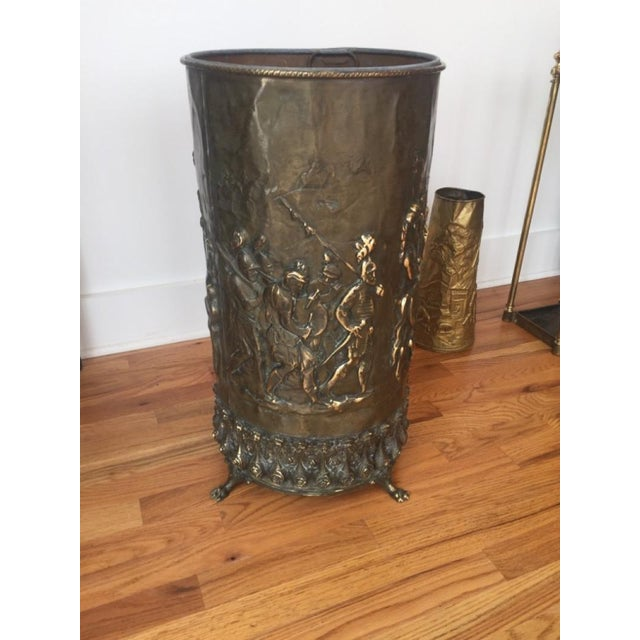 Large brass umbrella stand most probably used in a hotel lobby or office lobby. Military scenes cast throughout, with claw...