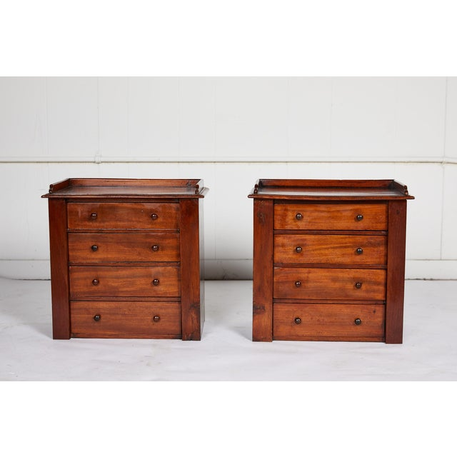 19th century charming English pair of miniature mahogany four-drawer chests with gallery lined tops and wooden knobs....