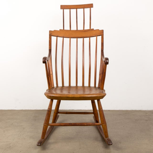 This mid-19th century New England pine Windsor rocker shows comb back styling with an extended shawl rack and is in...
