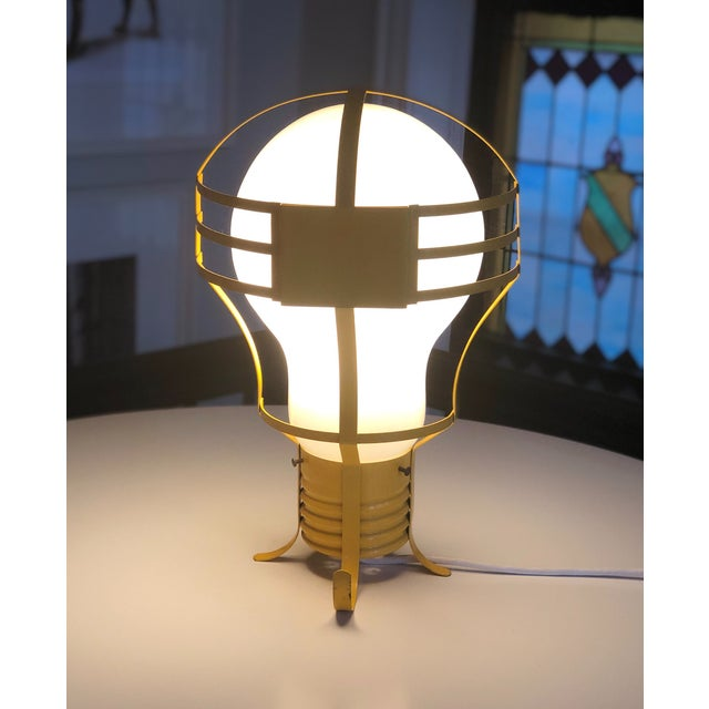 Funky Mid-Century light bulb lamp, with metal frame, glass bulb and yellow painted finish. Made in the 1960s - 60 watt...