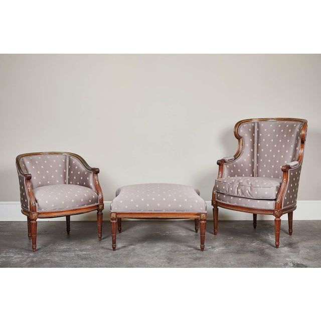 A set of two French chairs with ottoman having partially enclosed rounded heads and similar feet. Hardwood. Excellent...