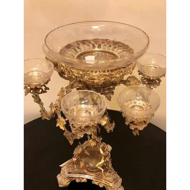 A silver plated finely cast centrepiece epergne with glass inserts. Of recent manufacture. Sure to add style and grace to...
